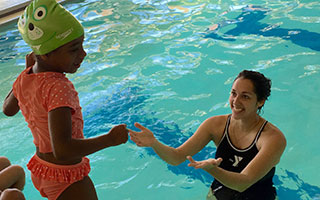 Swim instructor helps student