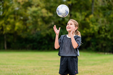 Girl bounces soccer ball off head